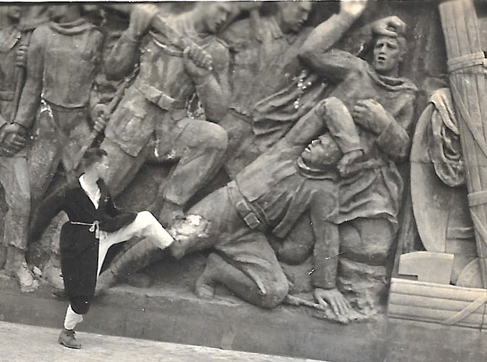 June 1944 - Emerson with foot on massive statue detecting men fallen in battle. His foot is placed directly on a leg wound of a spooning soldier.