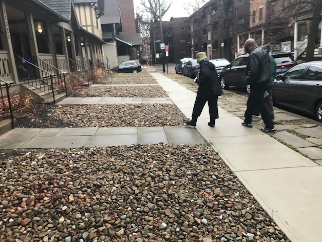 In front of Russell Berusch's rooming house, exploring the historically non-appropriate gravel yards and paved sidewalk are Counciman Blaine Griffin and Janice Cogger, a Hessler owner-occupier. Photo: Lee Batdorff