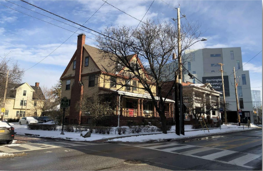 The March 18 meeting was held on the porch of 1975 Ford Dr. To its right is 1981 Ford Dr. These buildings will start renovations in May 2021. Photo provided by developer.