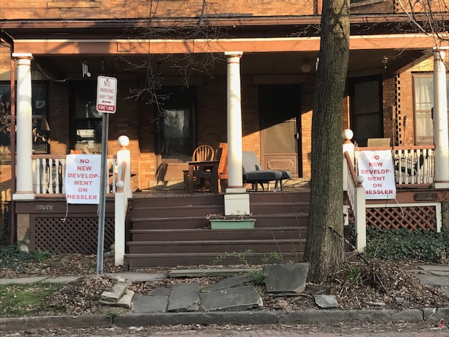 """Two porches on Hessler Road with """"No new development on Hessler""""."""